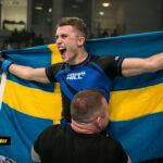 Zoran Milic håller upp den svenska flaggan efter vinst på IMMAF VM i Bahrain